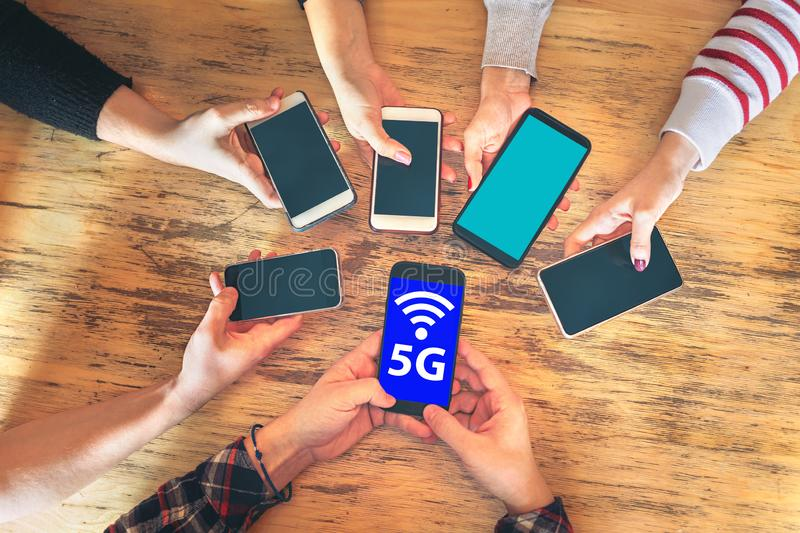 Friends group having fun together using 5G network connection on smartphones, Hands detail sharing wireless connection stock photo