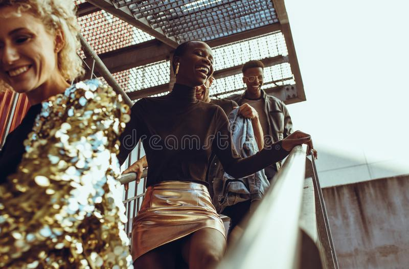 Friends hangout in the city. Multi-ethnic group of people walking down the steps and smiling. Friends hangout in the city on their weekend royalty free stock images