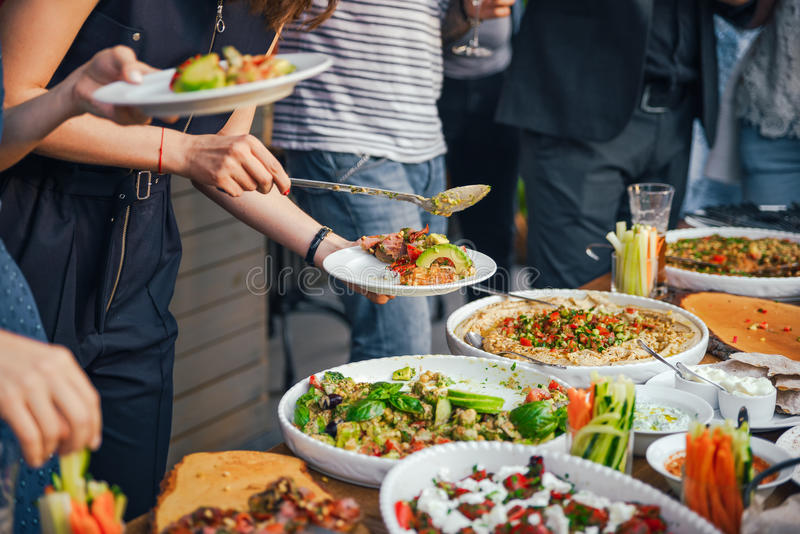 Friends Happiness Enjoying Dinning Eating Concept. Food Buffet. Catering Dining. Eating Party. Sharing Concept. Close-up stock photos