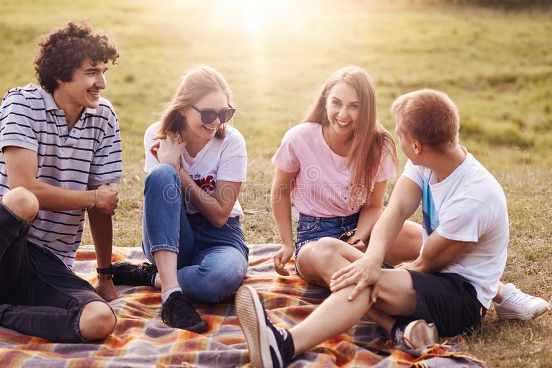Friends, happiness and leisure concept. Photo of friendly teenagers meet together on nature, have picnic, tell each other funny st royalty free stock image