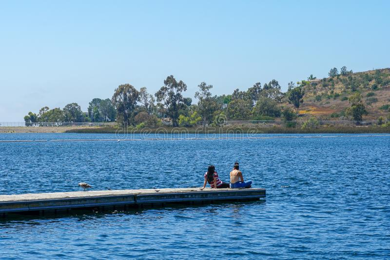 Yong girls sitting on the wooden pier and having a relax time. Friends happiness. Yong girls sitting on the wooden pier and having a relax time. Miramare Lake stock photography
