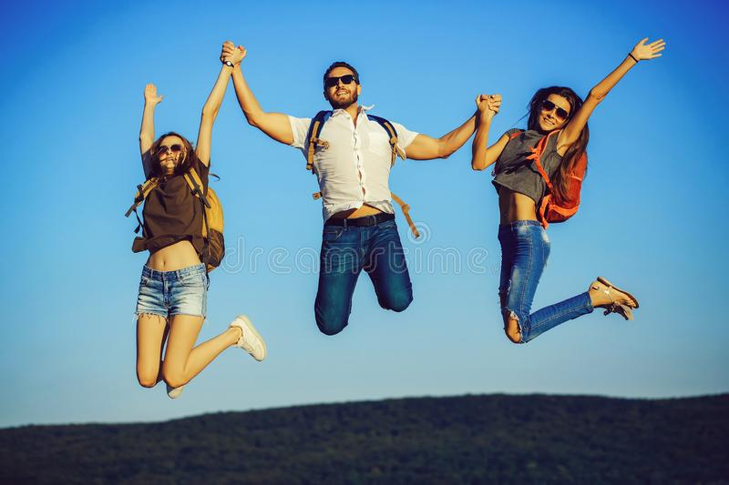 Friends, happy tourists jumping on mountain top on blue sky stock photos
