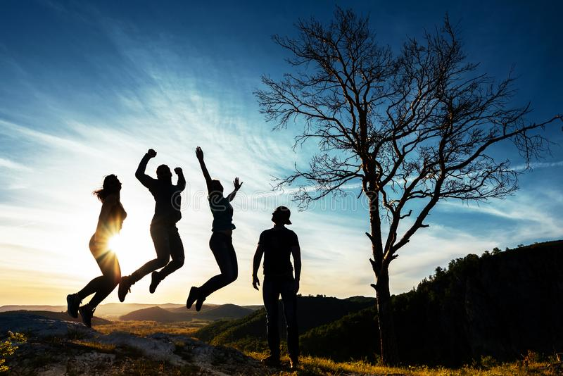 Silhouette of people. People in jump. Friends have fun at sunset. Funny friends. Best friends. Friends traveling. Group of people royalty free stock photo