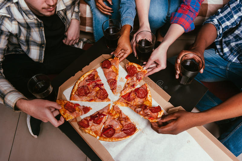 Friends have pizza party at home, fun leisure. Company of friends have pizza party at home, fun leisure. International friendship, company together, yummy royalty free stock photo