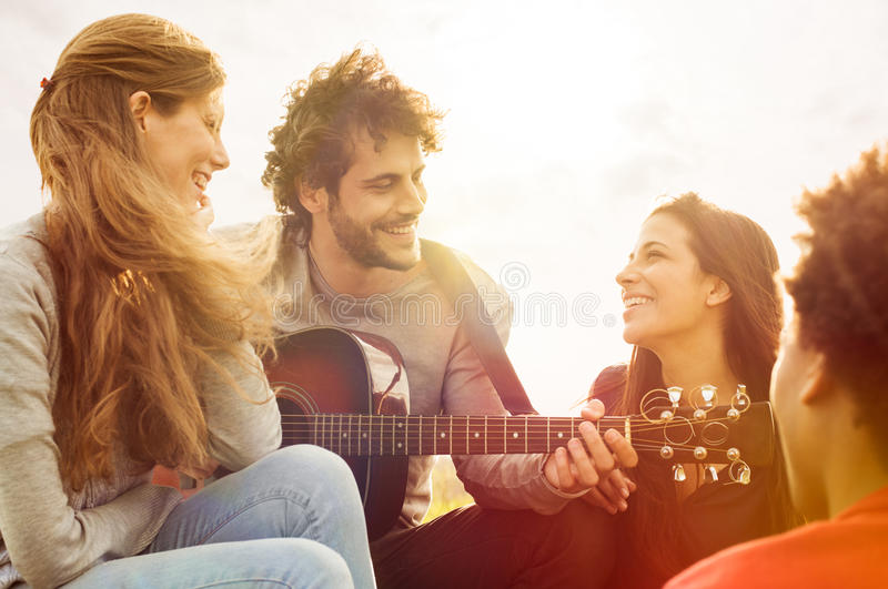 Friends Have Summer Fun. Happy group of friends enjoying the summer outdoor playing guitar and singing together stock images