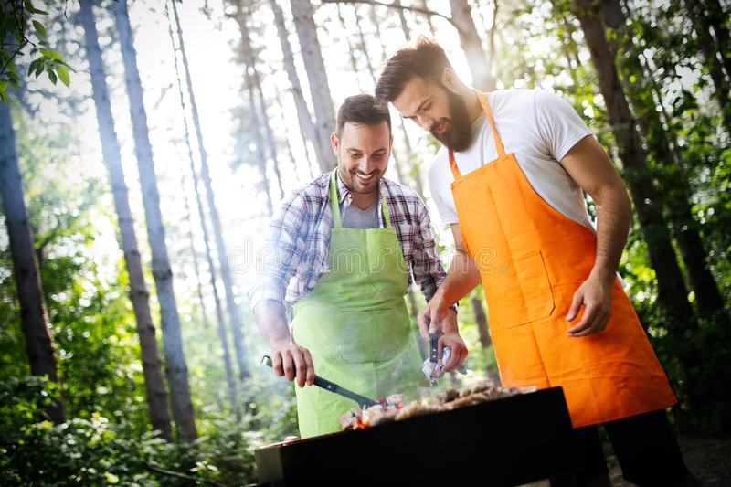 Friends having a barbecue party in nature while having fun stock photography