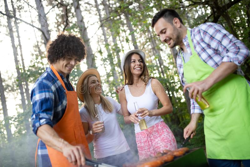 Friends having a barbecue party in nature while having fun royalty free stock photos