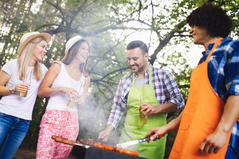 Friends having a barbecue party in nature while having fun stock image
