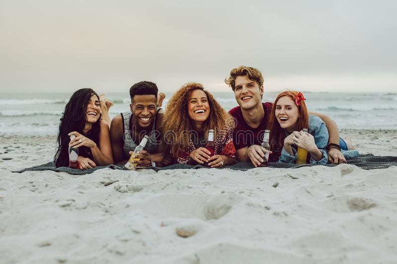 Friends having beers at the sea shore. Group of friends lying outdoors on a plaid with beer bottles. Young men and women having beers at the sea shore stock photography