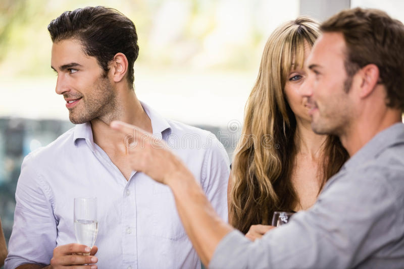 Friends having champagne and talking to each other stock images