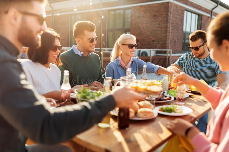 Friends having dinner or bbq party on rooftop royalty free stock photos