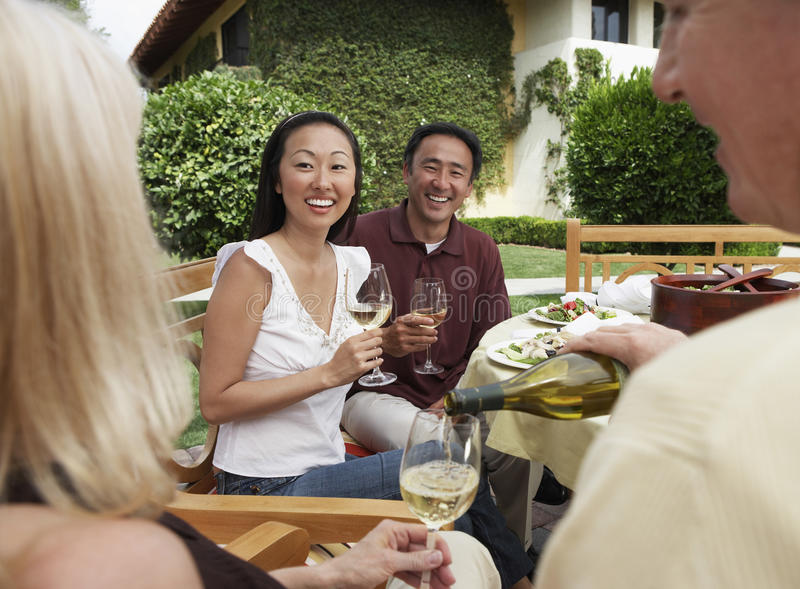 Friends Having Dinner And Drinks In Garden stock image