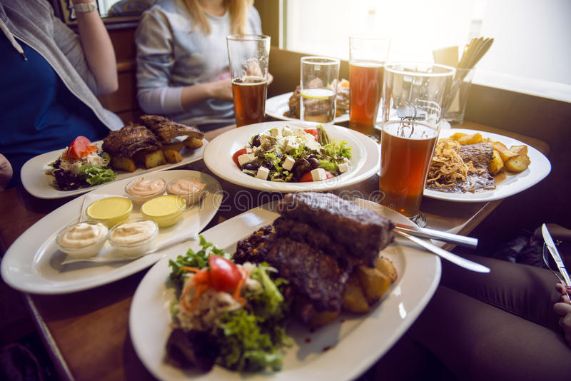 Friends having a dinner in the restaurant with salad, barbeque and beer royalty free stock images