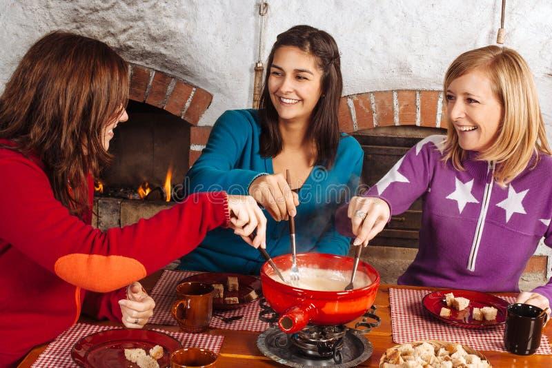Friends having fondue dinner royalty free stock images