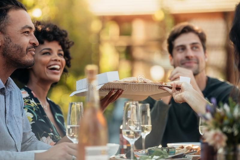 Friends having food at party outdoors. Group of young friends sitting around a table having food at party outdoors. Passing and serving food to friends royalty free stock photography