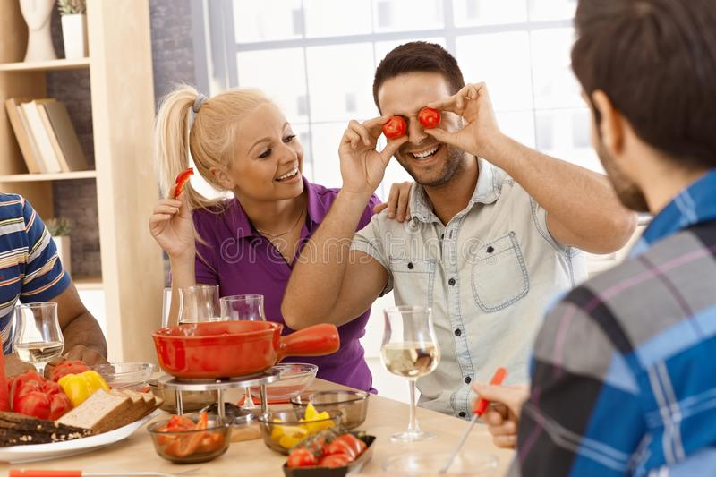Friends having fun around dinner table royalty free stock images
