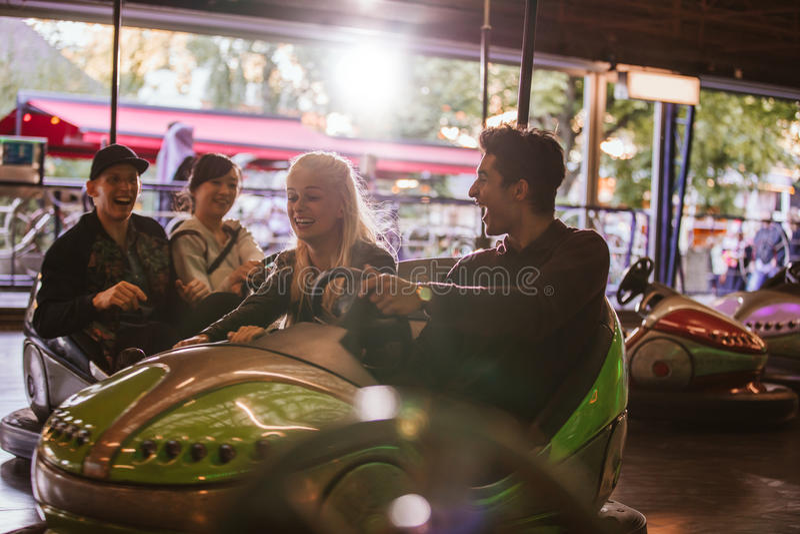 Friends having fun on bumper cars in amusement park royalty free stock photo