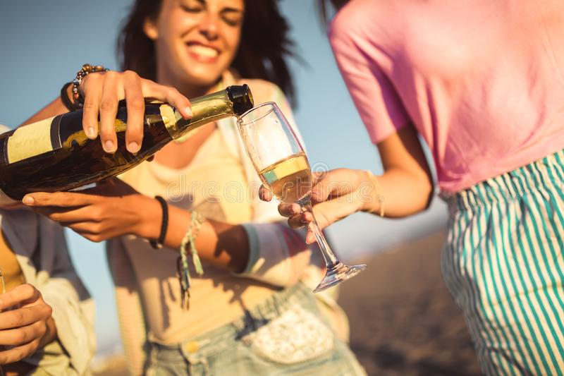 Friends having fun with champagne at celebration on beach. Selective focus royalty free stock photos