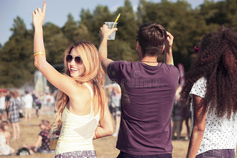 Friends having fun during concert. Group of three young friends having fun during an open air concert royalty free stock photography