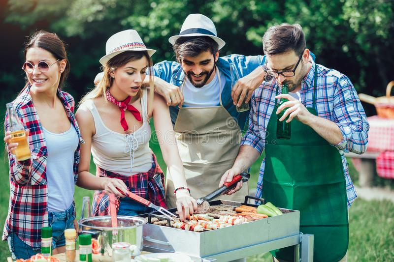 Friends having fun grilling meat enjoying barbecue party royalty free stock photography