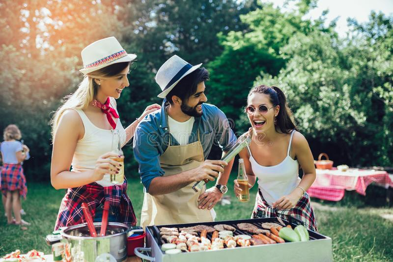 Friends having fun grilling meat enjoying barbecue party royalty free stock image