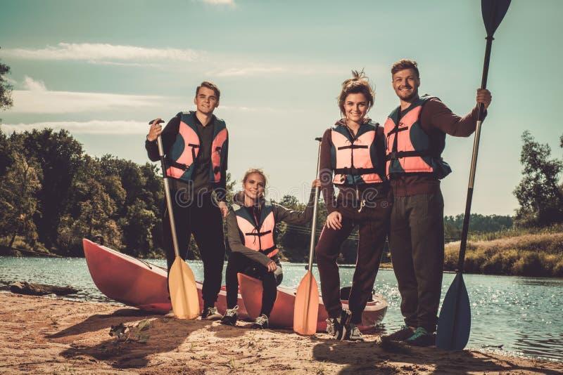 Friends having fun near kayaks on a beach. stock images