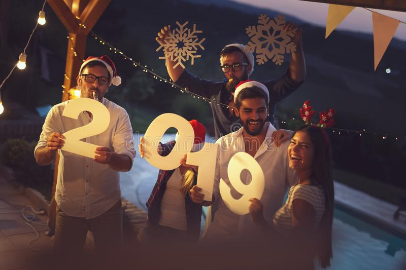 Friends having fun at a New Year`s Eve party by the pool stock photography