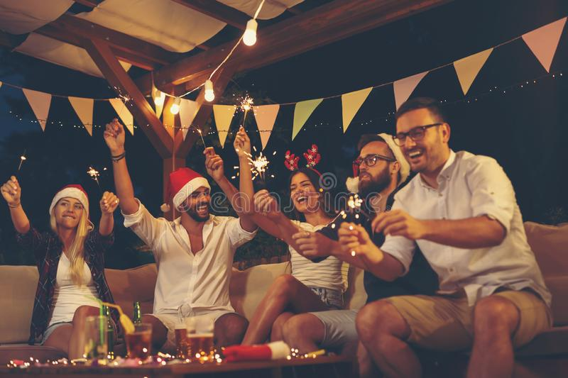 People waving with sparklers at New Years Eve party stock images