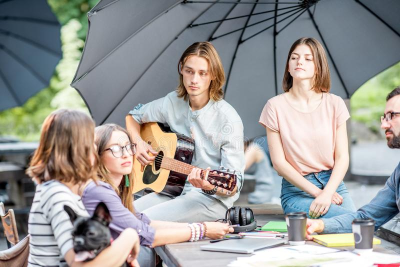 Friends having fun in the park. Young friends having fun together playing a guitar sitting at the table outdoors in the park royalty free stock image