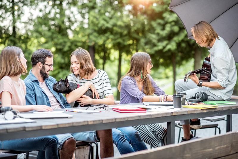 Friends having fun in the park. Young friends having fun together playing a guitar sitting at the table outdoors in the park stock photography