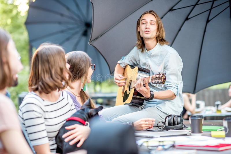 Friends having fun in the park. Young friends having fun together playing a guitar sitting at the table outdoors in the park stock images