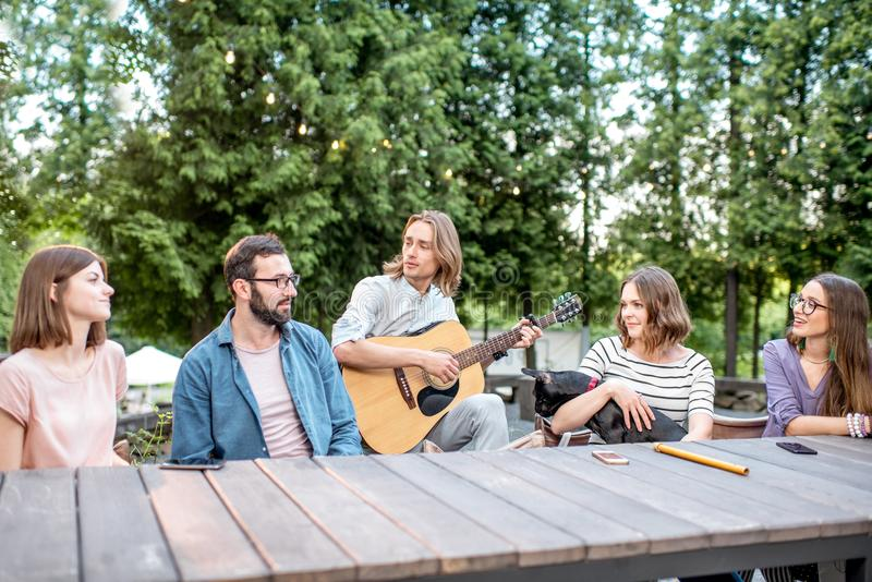 Friends having fun in the park. Young friends having fun together playing a guitar sitting at the table outdoors in the park royalty free stock photo
