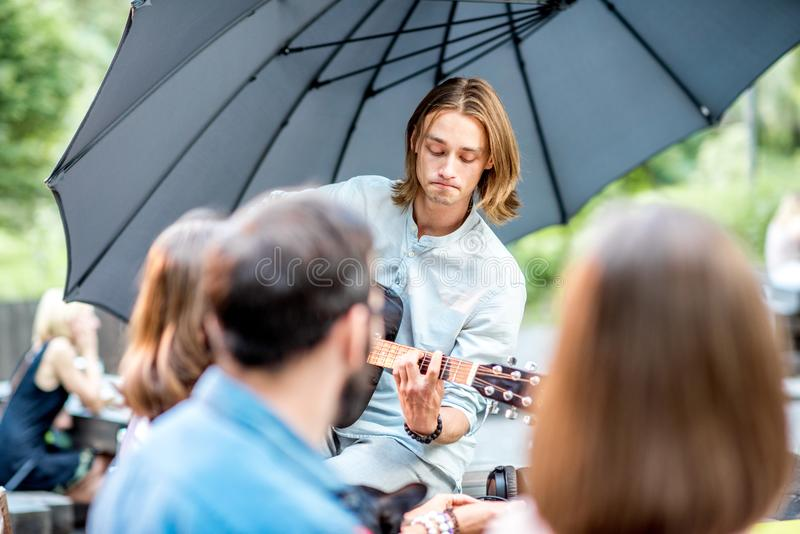 Friends having fun in the park. Young friends having fun together playing a guitar sitting at the table outdoors in the park royalty free stock photos