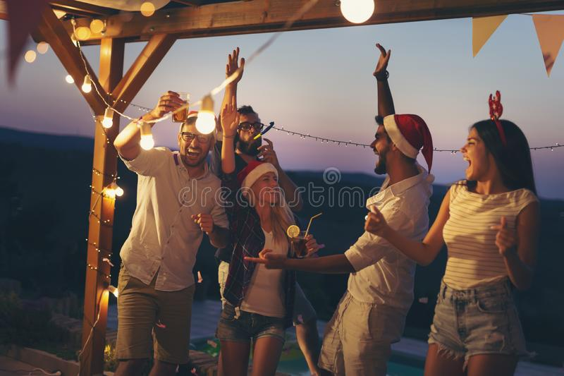 Friends dancing at poolside New Year`s Eve party stock photos