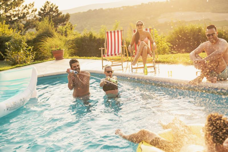 Friends having fun at a poolside party. Group of friends at a poolside summer party, having fun in the swimming pool, drinking beer and splashing water royalty free stock photo