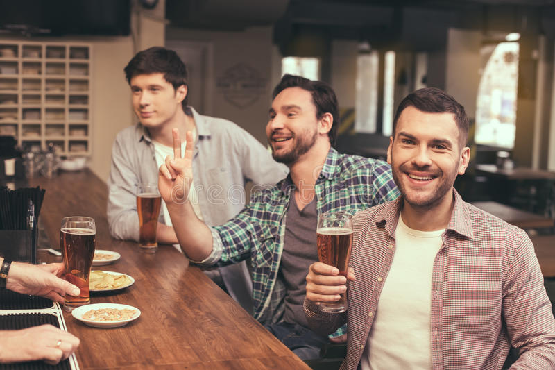 Friends having fun in pub. Football time. Friends spending time together in pub. Guys having fun while watching football. Men drinking beer royalty free stock photos