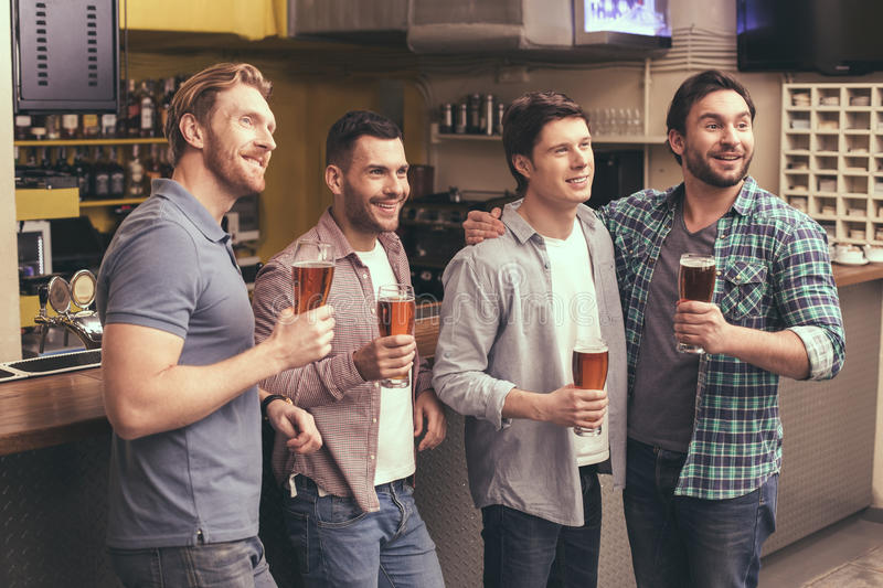 Friends having fun in pub. Football time. Friends spending time together in pub. Guys having fun while watching football. Men drinking beer royalty free stock photo