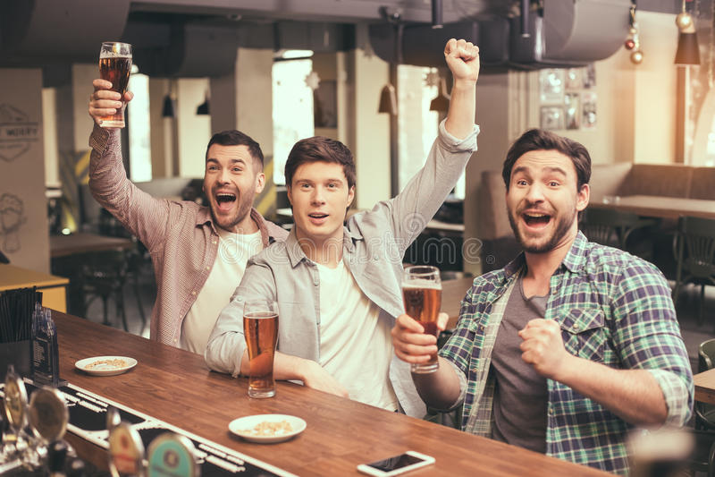 Friends having fun in pub. Football time. Friends spending time together in pub. Guys having fun while watching football. Men drinking beer royalty free stock images