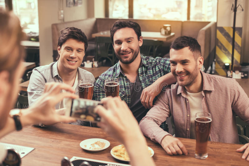Friends having fun in pub. Football time. Friends spending time together in pub. Guys having fun while watching football. Men drinking beer and making photo on royalty free stock image