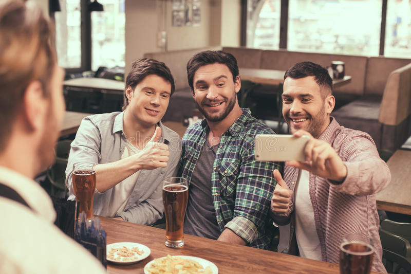 Friends having fun in pub. Football time. Friends spending time together in pub. Guys having fun while watching football. Men drinking beer and making photo on royalty free stock photos