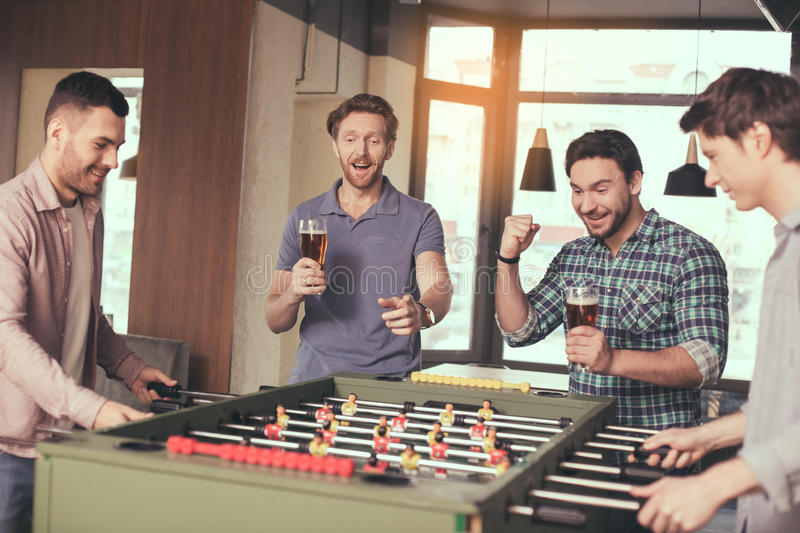 Friends having fun in pub. Table football. Friends spending time together in pub. Guys having fun while playing table football. Men drinking beer stock photography