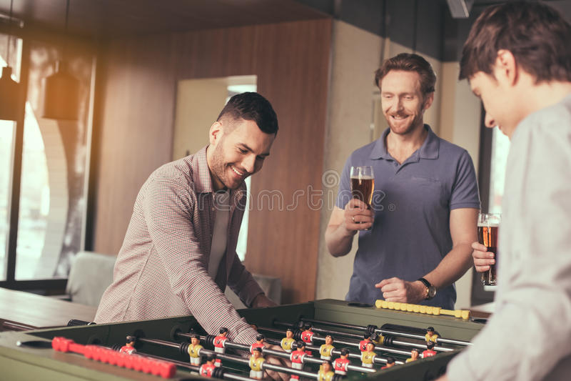 Friends having fun in pub. Table football. Friends spending time together in pub. Guys having fun while playing table football. Men drinking beer royalty free stock images