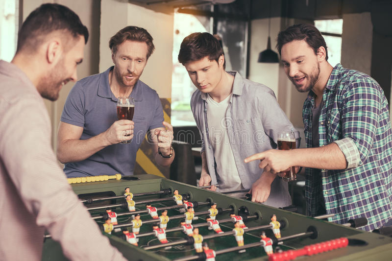 Friends having fun in pub. Table football. Friends spending time together in pub. Guys having fun while playing table football. Men drinking beer royalty free stock image