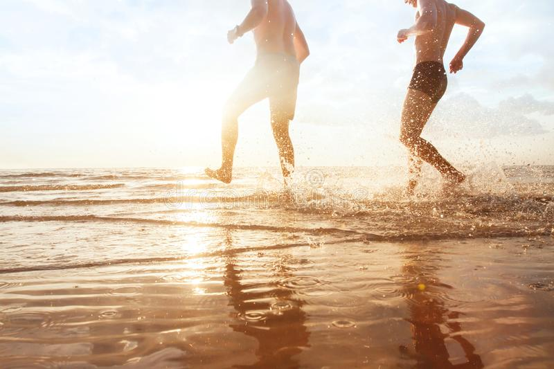 Holidays begin, happy friends running to the sea royalty free stock image