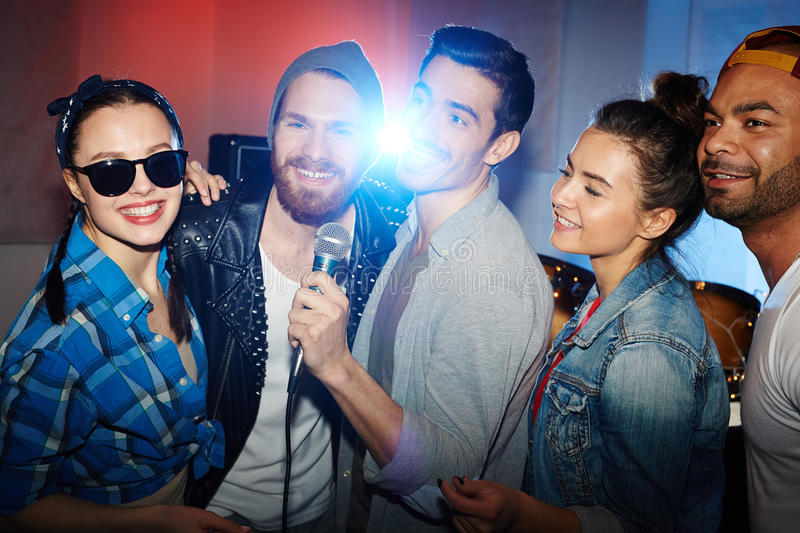Friends Having Fun on Stage in Club. Group of smiling party people, men and women, having fun on stage singing to microphone at night club party stock images