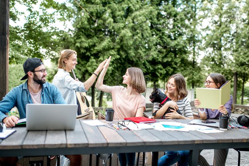 Friends having fun during a study outdoors. Young students having fun together meeting a friend while sitting with dog at the table outdoors royalty free stock photography
