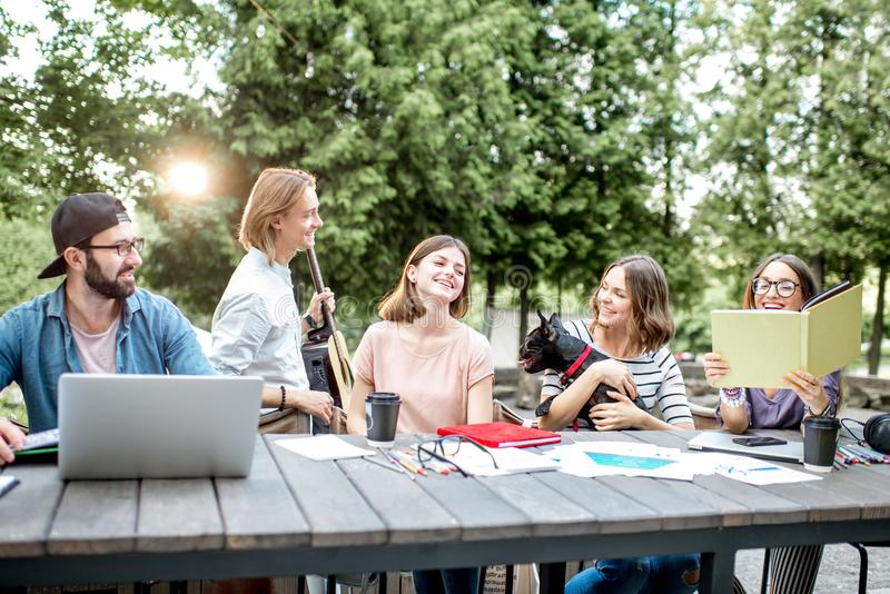 Friends having fun during a study outdoors. Young students having fun together meeting a friend while sitting with dog at the table outdoors stock photography