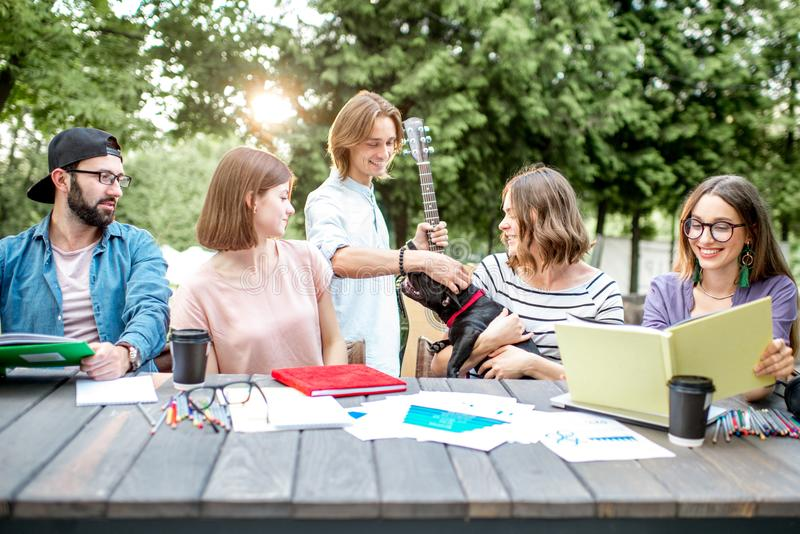Friends having fun during a study outdoors. Young students having fun together meeting a friend while sitting with dog at the table outdoors stock photo
