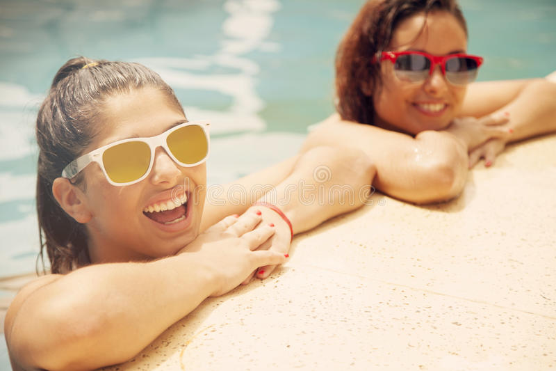 Friends having fun in swimming pool stock images
