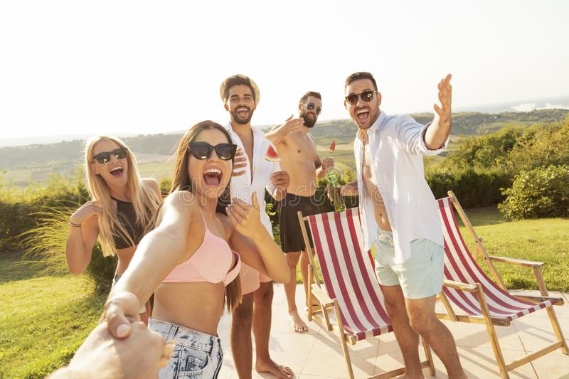 Friends having fun at a swimming pool party stock photography